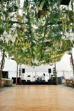 Amaranth, hydrangeas and fresh greens dangle around crystal chandeliers over the dance floor.