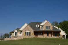 Custom home with stone veneer, a front porch with columns, board and batten shutters, and brick window molding.