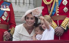 Britain's Catherine, Duchess of Cambridge holds her daughter Princess Charlotte and kneels by her son Prince George on the balcony of Buckingham Palace to watch a fly-past of aircrafts by the Royal Air Force, in London on June 11, 2016. Trooping The Colour and the fly-past are part of a weekend of events to celebrate the Queen's 90th birthday. / AFP / JUSTIN TALLIS