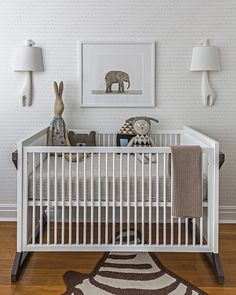 Lovely boy's nursery features white and gray baby elephant wallpaper, Sissy + Marley Baby Elephant Walk, adorned Sharon Montrose The Animal Print Shop's Baby Elephant Print flanked by Jonathan Adler Giraffe Sconces over black and white crib, ducduc Painted Campaign Crib, dressed in black and white ticking stripe crib bedding on Jonathan Adler Zebra Rug.
