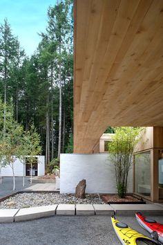 """""""Their lives revolve around ocean activities, reading, music, and good food and wine,"""" Jones says of the owners. """"The new house I designed is just for them,"""" such as with this sheltered outdoor areas where gear can be stored; the ceilings above are also Douglas fir."""