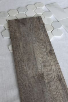 The bathroom floor will wear this tile. It looks like a weathered wood floor, but is ceramic. It is called Bayur Borneo.