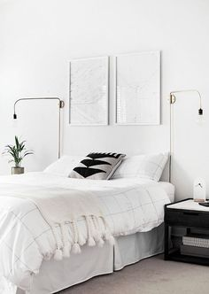 Minimalist white bedroom with gold sconces
