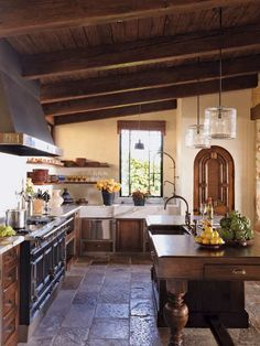 <3 this kitchen, especially the rustic look of the tiled floor and the beams on the ceiling...