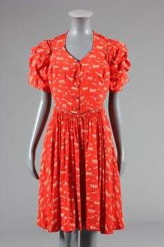 An unusual Jean Patou couture printed crepe de chine day dress, late 1930s, pink on white woven label and numbered 49 805, the tomato-red silk ground printed in white with figures based on Walt Disney's 1933 cartoon of the 'Three Little Pigs' -