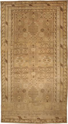 A Samarkand rug - A late 19th century Samarkand rug having a beige field and brown geometric motifs overall including angular pomegranate trellises within a b ...