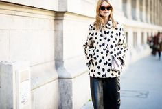 Pernille Teisbaek wears a polka dot cropped coat, leather pants, a crossbody bag, and sunglasses