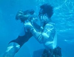 Nicolas Cage as Ben jumps in the pool and drinking a beer under water and Elisabeth Shue as Sera dives in and kisses him in Leaving Las Vegas 1995