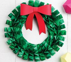 Spruce up a door with this easy-to-make folded paper wreath. All you need is a circular foam-core base, wide strips of green paper and a passion for crafts.