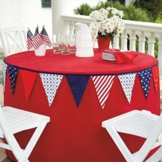 Great place for a banner! Patriotic circular patio table: drum-shaped red tablecloth, circled with red-white-blue banner, topped with small American flags in a white vase, milk glass white pitcher, and big clump of daisies.