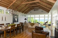 Living and dining room with hight wooden celing, wooden floor, leather armchairs, pendant lighting fixture. Project by Breese Architects and Interiors Studio Martha's Vineyard