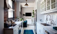 Loft kitchen features Thomas O'Brien Hicks Pendants over glass-front cabinets…