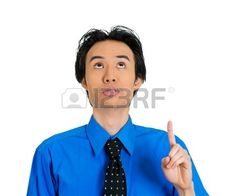 Closeup portrait of young business man pointing up looking at something above showing with index finger isolated on white background. Positive human emotion, facial expression, feeling, symbols, signs Stock Photo
