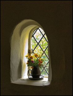 Flowers on a window sill at Cotehele House, Cornwall. This ancient house dating back to Jacobean times is still only lit with Candlelight.