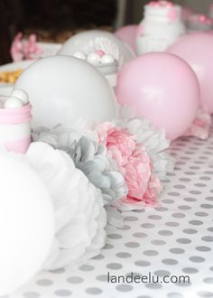 beautiful and thrifty baby shower centerpiece using tissue paper flowers, balloons and mason jars across a table runner of wrapping paper.