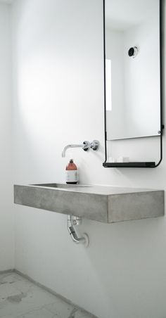 Minimal bathroom; integral black steel framed mirror with shelf; integral concrete sink and counterrop
