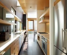 In this contemporary galley kitchen, clean, straight lines abound. Chunky yet minimalistic open shelving draws the eye seamlessly down through the length of the space. It is on this visual journey that we begin to notice the interesting architecture – planked ceiling over half of the kitchen and open airspace over the other half. Walls and flooring is a charcoal color, which, paired with a light neutral color palette of the cabinetry seems to expand the space overall.