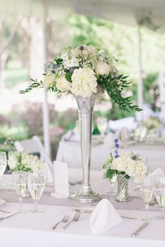 A tall silver vessel was topped with an arrangement of ivory roses and hydrangea blossoms, as well as blue delphinium blossoms and thistles. The centerpiece was flanked by two mercury-glass vases filled with similar florals. #whitecenterpiece #whiteweddingdecor Photography: Kelly Kollar Photography. Read More: http://www.insideweddings.com/weddings/alfresco-ceremony-romantic-tented-reception-in-new-jersey/594/