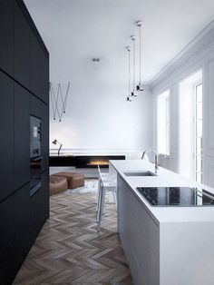 The Solid Dark Bank Of Units Contrasted With The Crisp White Kitchen Island  Is Perfectly Brought Together By The Tone And Pattern Of The Herringbone  Timber ...