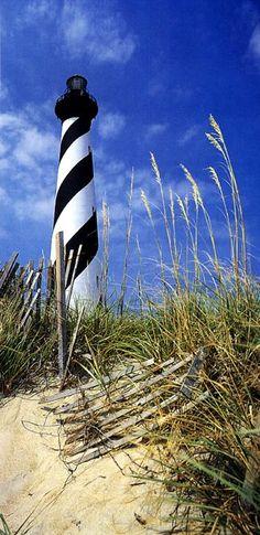 lighthouse, sand, sea oats, blue sky, fluffy clouds