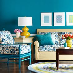 In this living room, a vivid cerulean blue colors the walls, and similar hues appear in the artwork, upholstery, and area rug, to carry the color through the space. A mid-tone khaki on the side table and sofa temper the blue, and mustard yellow accents provide further contrast.