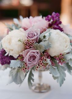Gorgeous centerpiece with White Peonies, Pink Wax Flower, Fuchsia Stock, Silverstone Roses, and Dusty Miller greenery.