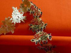 Ein faszinierendes Web Band.   Das Web Band hat die Grundfarbe gold.   Die Grundfarbe von dem Web Band glitzert leicht.   Die Farben von dem Webband sind gold, grün, orange und blau.   Das Web Band besteht aus einzelnen, an einander gereihten Blüten.  Auf den einzelnen Blüten wurden Perlen und Pailletten gestickt.  Sehr ausgefallen und Edel.  Die Perlen sind alle aufgenäht und nicht geklebt.   Die einzelnen Blüten sind ca. 4,8 cm breit und ca. 4 cm lang.