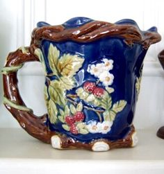 Beautiful majolica pitcher in deep cobalt blue with a delightful faux bois, raspberry bramble design motif. Chocolate brown vine encircles the pitcher and creates the handle while creamy white flowers, red berries and soft sage green leaves complete the decoration.