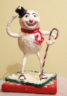 This adorable paper mache snowman was handmade by Robin Irlbeck. He features a chenille scarf and chenille stem candy cane.    His wooden base is 6in by 6in, the entire piece is 9.75in tall.