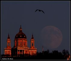 Gibbous Moon rising alongside the Superga Church on the Turin hill, Italy. Piemonte