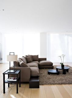 .Instead of forming a room in an open concept by closing an area off with furniture...keep the space open by letting the rug mark off the edge of the space.