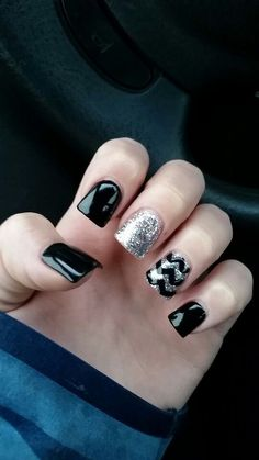 Cool Black shellac gel polish on acrylic fake nails with a sparkly glittery silver ac...