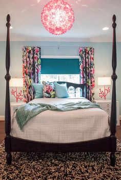 Gorgeous bedroom with a pink capiz chandelier over the black four poster bed