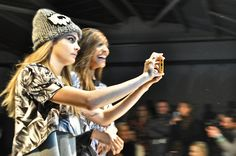 Cara Delevingne taking a selfie video on the Giles runway at London Fashion Week fall/winter 2014/15