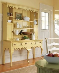 I love this piece of furniture in this great buttery color!  The items displayed on it are appropriate to style and time period, with vintage look ceramics, spice jars, and photo.  It is well-arranged without being crowded or stiffly symmetrical.  My favorite piece is the wonderful black bird!