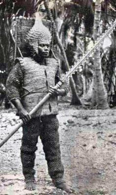 Kiribati (Gilbert Islands) warrior with porcupine fish helmet, shark tooth sword and armour made from coconut fibre. Early 1900s.