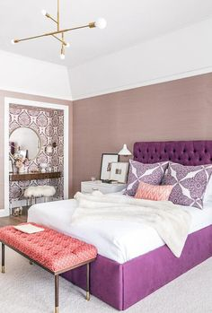 Purple bedroom features walls clad in purple grasscloth by Schumacher lined with a  purple velvet tufted bed dressed in purple shams in John Robshaw fabric next to a white lacquered nightstand adorned with brass pulls illuminated by a white modern wall sconce alongside a pink bench upholstered in shell print fabric, Katie Ridder Wave fabric, placed at the foot of the bed illuminated by a brass modular pendant light.