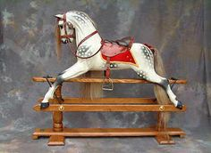 Legends' 'New' Traditional Dapple Grey Rocking Horse  Legends' own rocking horse carving design in a very light colour with black dappling. Red saddle blanket with gold trim,tan leather tack and mid grey/brown mane and tail. Legends Rocking Horses