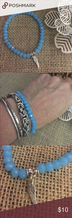 Blue Glass Stretch Bracelet Blue glass Bead Stretch bracelet with a half angel wing . Add to your stack or start your stack today !  The charm is metal alloy with Rhodium plating.  I have several colors listed, bundle and save!  Z09 Jewelry Bracelets
