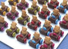 Teddy Bear Race Cars 1 packet of mini Mars Bars or Milky Way chocolate bars 1 family packet of smarties 1 box of Tiny Teddy biscuits 1 quantity of icing sugar icing paste for glue ( mix half cup of icing sugar and a teaspoon of cocoa powder with a few drops of hot water) Glue each of the 4 wheels (smarties) on to the sides of the milky way bars. Press into each centre a tiny teddy biscuit. Glue on a smartie steering wheel for each one.