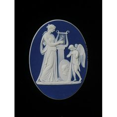White Jasperware flat oval with dark blue dip. Applied white bas-relief decoration, mimicking the effect of a classical carved cameo shell, depicts the classical subject of a muse and a genius. The robed muse faces right playing a lyre on a pedestal. A shield with a profile portrait rests on the base, in front of a winged youth leaning on a long straight trumpet. The front edge of the cameo is bevelled and polished. ca.1780-1800
