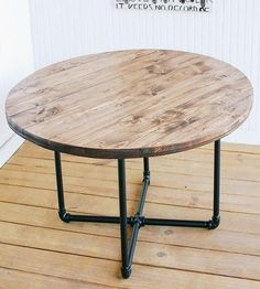 Give your coffee cups and art books a new home with this rustic coffee table. Reclaimed wood is pieced into a circular shape and stained a dusty red hue. The tabletop is perched on a pipe leg base, for industrial flair.