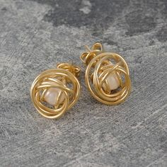 Caged Pearl Gold Knot Earrings in White - A striking, contemporary design featuring exquisite and intricate craftsmanship where a single, white freshwater pearl is cleverly encased within a gold wire cage to create these Caged Pearl Gold Knot Earrings in White. #Otisjaxon #Jewellery #MothersDay #Present