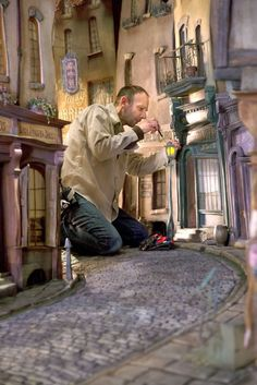 "Set designer creating a fantastical street scene for ""The Boxtrolls"". The film used some CGI but was mostly stop-motion animation. Models Men, Laika Studios, Kubo And The Two Strings, Arte Sketchbook, Tiny World, Stage Set, Illustration, Autumn Art, Behind The Scenes"