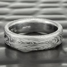 Our BOOKMATCHED pattern 6mm wide ring is inspired by the amazing woodworking tradition utilized in fine cabinet and instrument making. In this technique a thick board is sawn in half and then opened like a book. These halves are joined, and the grain of the two halves create an organic mirror image. We use proprietary carving and forging techniques to achieve the same look in our solid stainless steel BOOKMATCHED pattern rings.
