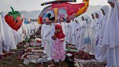 طفلة إندونيسية تستمتع بأكل الآيس كريم والنساء من حولها يؤدون صلاة العيد على شاطى
