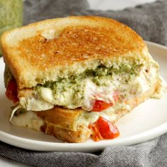 Caprese Grilled Cheese: loaded with basil pesto, a thick and chunky garlic butter tomato sauce, and fresh mozzarella cheese, all on grilled sourdough bread. The literal taste of summer. #vegetarian #lunch #sandwich #recipe #simplerecipe #dinner | pinchofyum.com Sponsored by @landolakesktchn