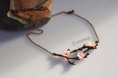 ✿ Hand Clayed Cherry Blossom on Copper Twig & Chain For this necklace I clayed 3 tiny pink cherry blossom flowers, which I attached to an antiqued copper twig and chain. The copper has a darkened red look, and the lighter flowers stand out. The necklace work well as a short / little