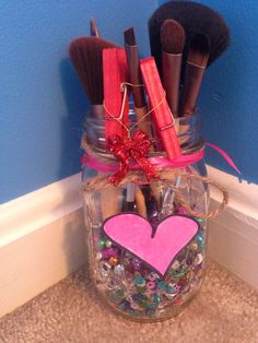 DIY mason jar valentines day makeup brush holder idea!  Steps:  1:gather materials such as mason jar, beads of choice,yarn,ribbon,paper,and makeup brushes if you want you can have the clips as shown in the photo! 2:pour the beads in 3:trace a heart on your paper and cut it out! 4:color the heart in 5:put ribbon and yarn at the top and put any decorations of your choice!  That's it and then just put your makeup brushes in and you have completed this simple valentines day DIY!  Xoxo,megan✄