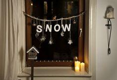 Winterliche Fensterdeko mir Schnee und einem kleinen Hirsch.